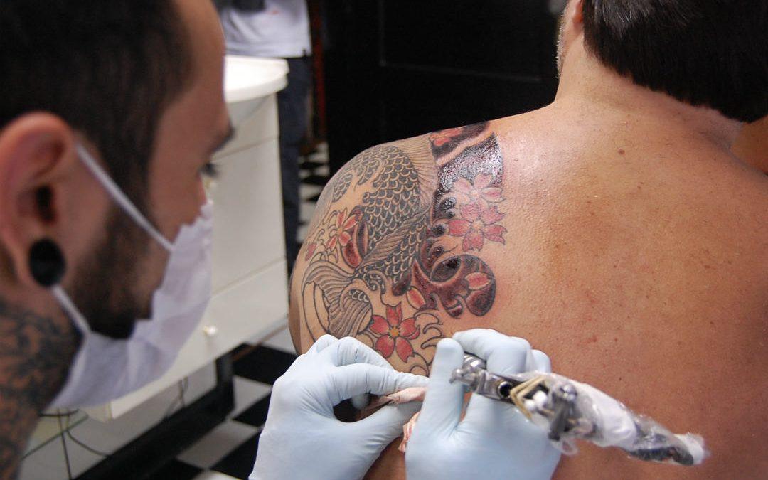 Un homme se faisant tatouer le dos./photo: Micael Faccio