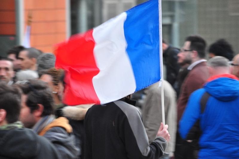 Une personne brandit le drapeau français en attendant de pouvoir entrer. (Photo : Le24heures.fr/Léo Rebeyrol).